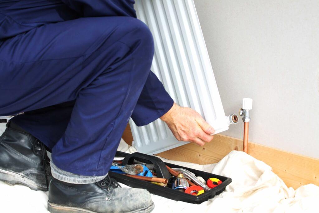 Plombier en train de démonter un radiateur
