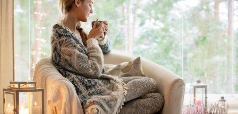 Femme buvant boisson chaude dans canapé sous un plaid