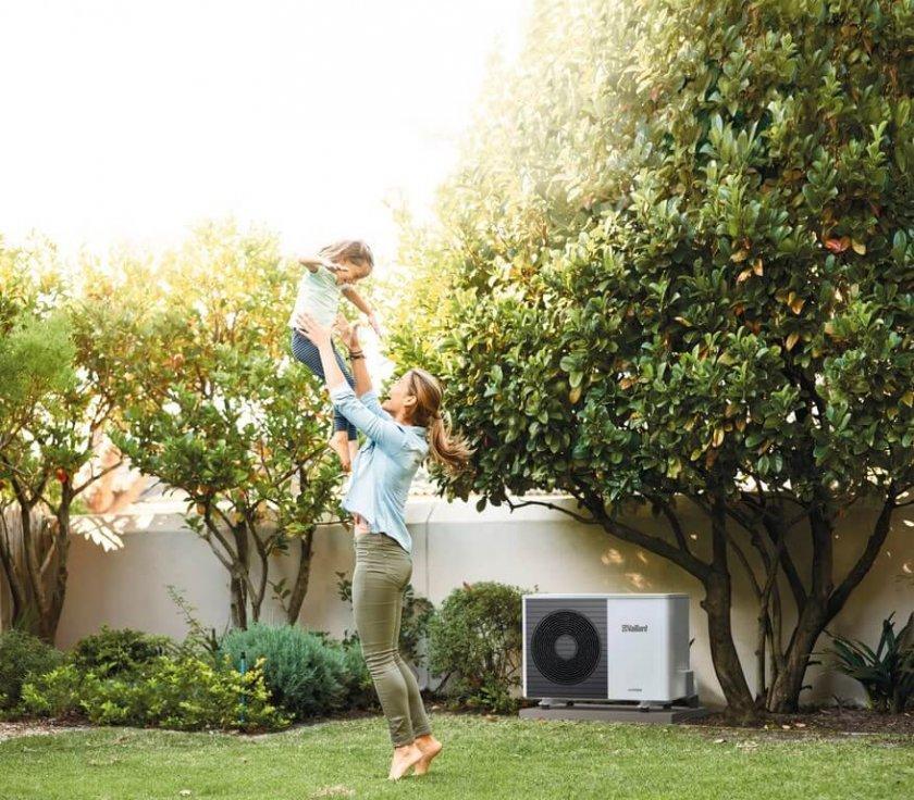 Pompe à chaleur dans un jardin avec une famille en train de jouer