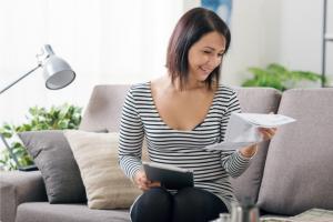 Femme assise dans un canapé en train de lire une facture de gaz naturel