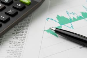 Stylo et calculette posés sur une feuille de budget avec graphique de fluctuation de prix