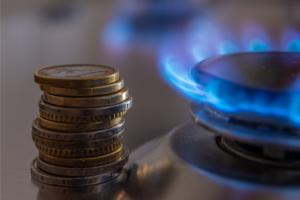Plaque de cuisson gaz naturel en marche et pièces de monnaie posées à côté