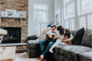 famille jouant sur un canapé à l'interieur d'une maison