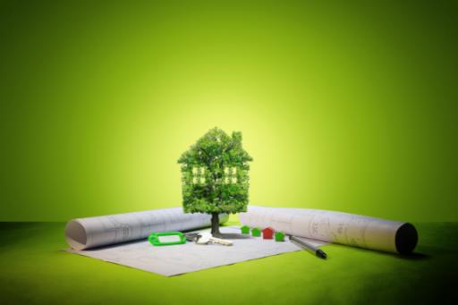 maison en feuilles vertes posée sur un plan un stylo et des clefs